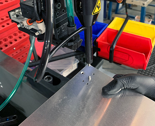 Panel is accurately located on the machine and the insert is automatically fed into position.